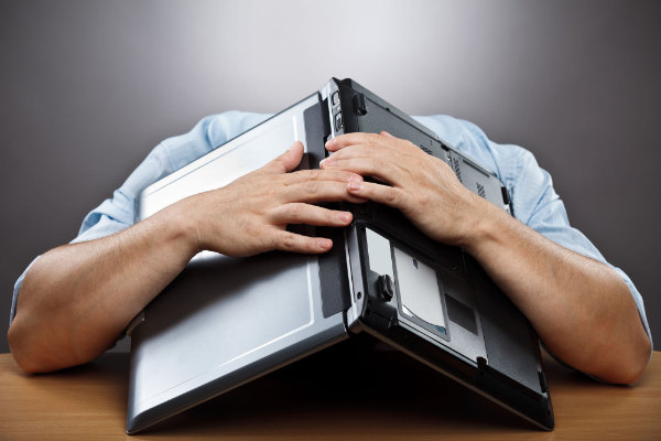 Man hiding head underneath an open laptop